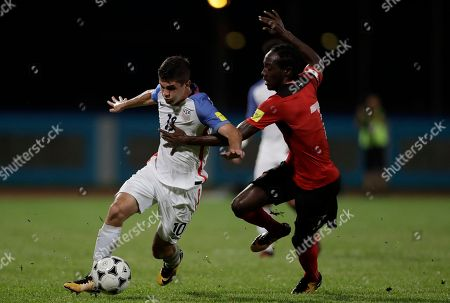 United States' Christian Pulisic, left, fight for the ball with Trinidad and Tobago's Nathan Lewis during a 2018 World Cup qualifying soccer match in Couva, Trinidad