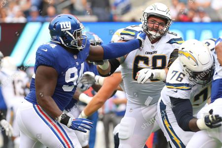 Dalvin Tomlinson, Matt Slauson. New York Giants defensive tackle Dalvin Tomlinson (94) rushes against Los Angeles Chargers offensive guard Matt Slauson (68) during an NFL football game, in East Rutherford, NJ. The Chargers won 27-22