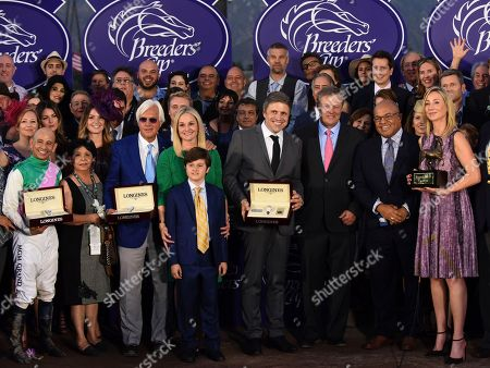 Juan-Carlos Capelli, center, VP and Head of International Marketing, Longines, presents Conquest Classic timepieces to jockey Mike Smith, left, trainer Bob Baffert, third left, and Garrett O'Rourke, center right, Manager, Juddmonte Farms, after their horse Arrogate wins the Breeders' Cup Classic, at Santa Anita Park in Arcadia, CA, as Belinda Stronach, right, Chairman and President, The Stronach Group, looks on. Longines, the Swiss watch manufacturer known for its elegant timepieces, is the Official Watch and Timekeeper of the Breeders' Cup World Championships and the Triple Crown