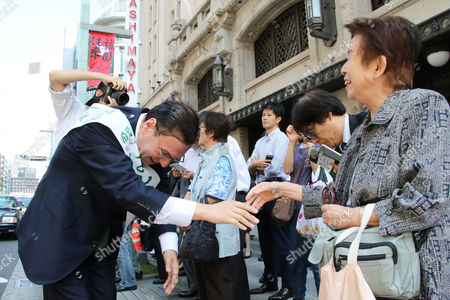 Taro Hatoyama (L), a candidate for Tokyo Governor Yuriko Koike's Party of Hope shakes hnds with a voter during a general election campaign in Tokyo on Tuesday, October 10, 2017.