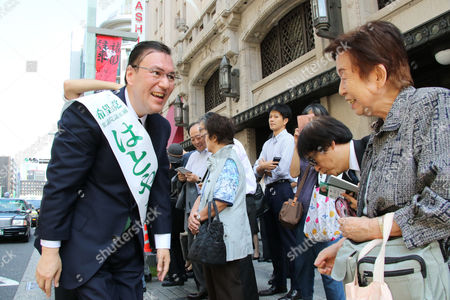 Taro Hatoyama (L), a candidate for Tokyo Governor Yuriko Koike's Party of Hope shakes hands with a voter during a general election campaign in Tokyo on Tuesday, October 10, 2017.