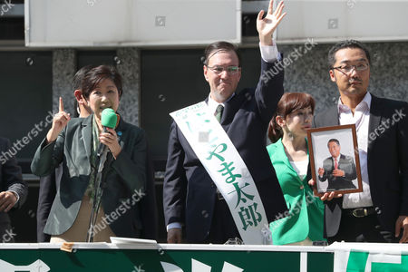 Tokyo Governor and leder of the Party of Hope Yuriko Koike (L) delivers a campaign speech for her party candidate Taro Hatoyama (C) during a general election campaign in Tokyo on Tuesday, October 10, 2017.