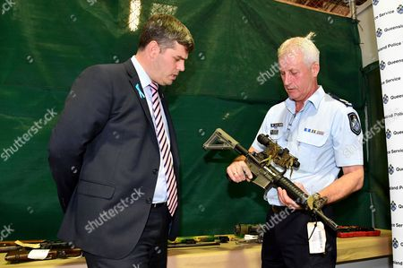 Queensland Minister for Police, Fire and Emergency Services Mark Ryan (L) is shown one of the confiscated firearms by Senior Sergeant Steve Bullock (R) in Brisbane, Queensland, Australia, 12 October 2017. Minister Ryan announced that Queenslanders have handed in over 16,000 firearms as part of the national gun amnesty.