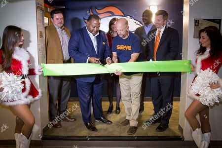Brady Kellogg, Denver Broncos, from left, Lamont Brooks, CenturyLink, Brad Meuli, President/CEO Denver Rescue Mission, Amy Carlson, CenturyLink, Vernon Irvin, SVP of Small & Midsize Business CenturyLink, and Rich Karlis, CenturyLink, seen at the Ribbon Cutting for the technology upgrade to the Denver Broncos Youth Center located in the Denver Rescue Mission Youth Center at The Crossing Facility on in Denver Colorado. Computers, laptops, projector and network technology was donated by CenturyLink