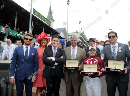 Actor and Longines Ambassador of Elegance Simon Baker, left, joins Jennifer Judkins, second left, and Juan-Carlos Capelli, third left, both of Longines, to award trainer Steve Asmussen, jockey Rosie Napravnik and owner Ron Winchell, left to right, with their Longines timepieces after their horse Untapable won the Longines Kentucky Oaks on Kentucky Oaks Day, in Louisville, Ky. Longines, the Swiss watch manufacturer known for its luxury timepieces, is the Official Watch and Timekeeper of the 140th annual Kentucky Derby