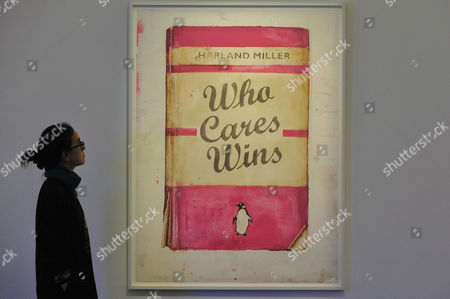 """A staff member views """"Who Cares Wins"""", 2017, by Harland Miller (Est. GBP20-25k) at a preview of artworks for the """"Art for Grenfell"""" auction taking place"""