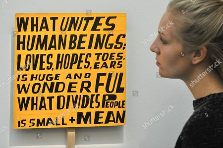 "A staff member views ""What Unites Human Beings"", 2017, by Bob and Roberta Smith (Est. GBP2.5-3.5k) at a preview of artworks for the ""Art for Grenfell"" auction taking place"