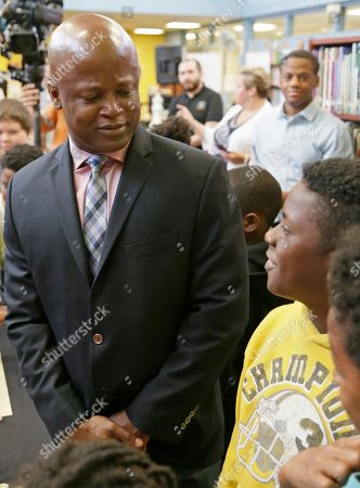 Chess Grand Master Maurice Ashley does a little light-hearted trash talking with a student at a news conference to announce an initiative by Ascension and the St. Louis Chess club to start chess clubs in the schools of the Ferguson-Florissant school district, at Walnut Grove