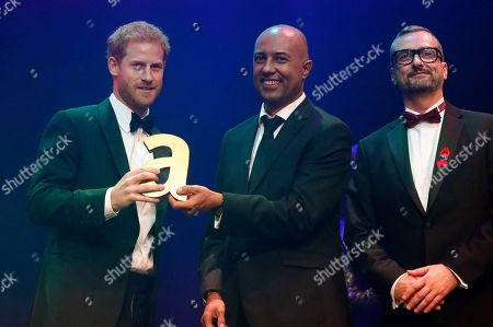 Britain's Prince Harry, left, receives a posthumous Attitude Legacy Award on behalf of his mother Diana, Princess of Wales, from Ian Walker, right, and Julian La Bastide at the Attitude Awards in London, . Attitude Magazine is awarding the prize to the late Princess Diana in honour of her significant work in drawing attention to HIV/AIDS