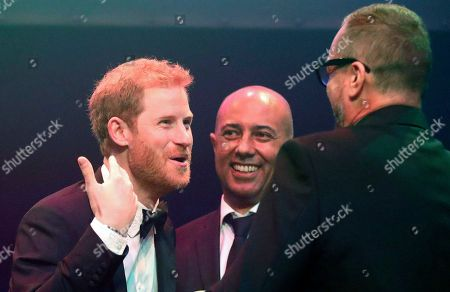 Britain's Prince Harry, left, reacts as he receives a posthumous Attitude Legacy Award on behalf of his mother Diana, Princess of Wales, from Ian Walker, right, and Julian La Bastide at the Attitude Awards in London, . Attitude Magazine is awarding the prize to the late Princess Diana in honour of her significant work in drawing attention to HIV/AIDS