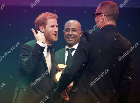 Stock Image of Britain's Prince Harry receives a posthumous Attitude Legacy Award on behalf of his mother Diana, Princess Diana, from Ian Walker, right, and Julian La Bastide at the Attitude Awards