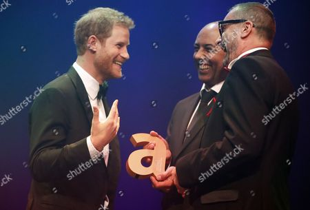 Stock Photo of Britain's Prince Harry receives a posthumous Attitude Legacy Award on behalf of his mother Diana, Princess Diana, from Ian Walker, right, and Julian La Bastide at the Attitude Awards in London, Thursday, Oct. 12, 2017. Attitude Magazine is awarding the prize to the late Princess Diana in honour of her significant work in drawing attention to HIV/AIDS. (AP Photo/Frank Augstein, pool)