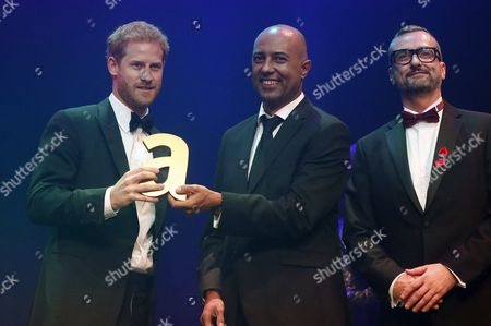 Britain's Prince Harry, left, receives a posthumous Attitude Legacy Award on behalf of his mother Diana, Princess Diana, from Ian Walker, right, and Julian La Bastide at the Attitude Awards
