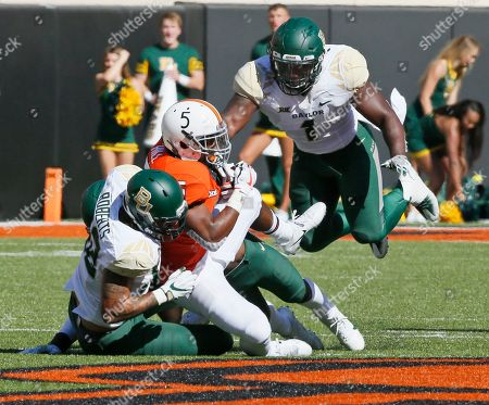 Justice Hill, Greg Roberts, Taylor Young. Oklahoma State running back Justice Hill, center, is brought down by Baylor's Greg Roberts, left, and Taylor Young (1) in the first quarter of an NCAA college football game in Stillwater, Okla