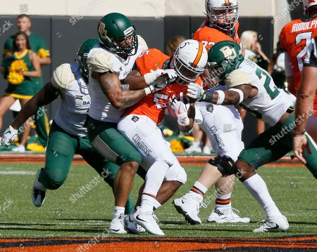 Justice Hill, Greg Roberts, Henry Black. Oklahoma State running back Justice Hill, center, is brought down by Baylor's Greg Roberts, left, and Henry Black, right, in the first quarter of an NCAA college football game in Stillwater, Okla