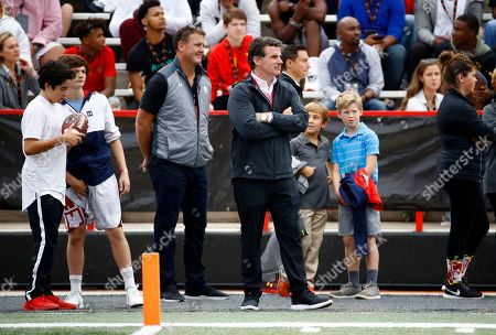 Under Armour CEO Kevin Plank, center, stands on the Maryland sideline during an NCAA college football game between Maryland and Northwestern in College Park, Md