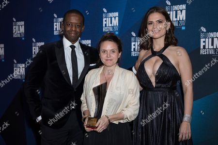 Adrien Lester, Lucy Cohen, Hayley Atwell. Documentary competition winner Lucy Cohen, center poses for photographers along with Adrien Lester and Hayley Atwell after receiving the Grieson award for her film 'Kingdom of Us' at the London Film Festival Awards in London