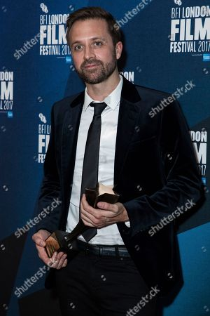 Stock Picture of Director John Trengove poses for photographers after receiving the Best Feature Film award for his film 'The Wound' at the London Film Festival Awards in London