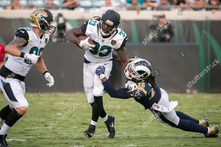 Jacksonville Jaguars running back Chris Ivory (33) runs the ball against the Los Angeles Rams linebacker Mark Barron (26) during the first half of an NFL football game, in Jacksonville, Fla