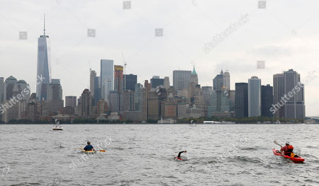 """Stock Picture of Martin Strel approaches the Freedom Tower in Downtown Manhattan as he swims from the Statue of Liberty to North Cove Marina, in New York. On March 22, 2016, World Water Day, Strel will commence his """"Strel World Swim"""" through 107 countries in approximately 450 days as a means of spreading clean water awareness"""