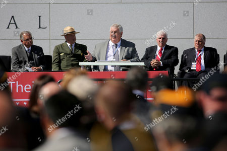 Dennis Joyner, center, speaks during the dedication ceremony of the American Veterans Disabled for Life Memorial while Ray LaHood, left, Robert Vogel, Gene Murphy and Roberto Barrera look, in Washington