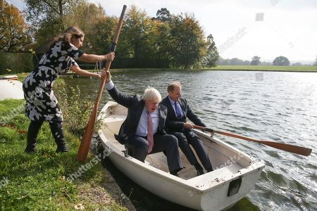 British lawyer and Boris Johnson's wife, Marina Wheeler assists Britain's Foreign Secretary Boris Johnson, left, as he boards a row boat with Czech Republic's Deputy Foreign Minister Ivo Sramek, on a lake within the grounds of Chevening House, the British foreign secretary's official residence, in southern England, . Johnson held talks with visiting delegations from European foreign ministers to discuss shared challenges and European security