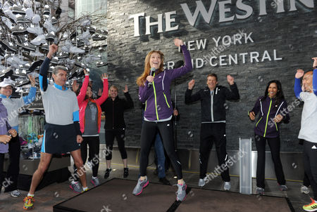 Stock Image of Padma Lakshmi, right, joins Brian Povinelli, second right, Global Brand Leader, Westin Hotels & Resorts, as Holly Perkins, center, New Balance Fitness Ambassador, leads a warm-up stretch on to kick off the New York City 5K run in celebration of the global launch of Westin's New Balance gear lending program. Thousands of associates around the world ran in support of the brands' pledge to donate 15,000 pairs of shoes to Soles4Souls and Hurricane Sandy relief