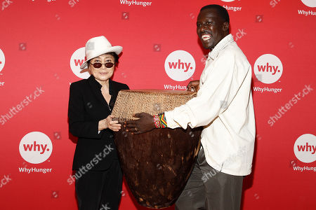 "Okello Sam, right, founder of Hope North, Uganda, part of WhyHunger's ""Imagine There's No Hunger"" campaign, presents ASCAP Harry Chapin Humanitarian Award winner Yoko Ono Lennon with a handmade drum at the WhyHunger Chapin Awards on in New York"