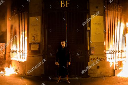 Russian artist Petr Pavlensky poses in front of a Banque de France building after setting fire to the window gates as part of a performance in Paris, . Pavlensky, known for macabre, politically charged actions, was being detained by police