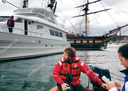 Deckhand Tucker Wheeler, left, and executive director Jessica Wurzbacher, of the tall ship SSV Oliver Hazard Perry, right, take a small boat tour of Newport Harbor, in Newport, R.I., to view damage to boats struck by the tall ship, which lost power and began to drift in the harbor Sunday night