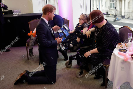 In his capacity as patron of the charity WellChild, Britain's Prince Harry meets Katie Ward, aged 10, the winner of the Inspirational Child Award aged 7-10, with her mother Ruth during a pre-ceremony category winners reception at the Royal Lancaster Hotel in London, . The prince attended the annual WellChild awards Monday for the charity, who help to get seriously ill children and young people out of hospital and home to their families