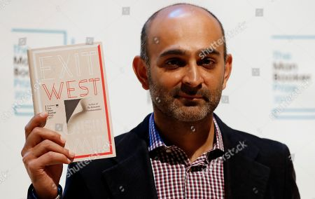 Author Mohsin Hamid of Britain and Pakistan with his book 'Exit West' during a photocall with all six shortlisted authors of the 2017 Man Booker Prize for Fiction, in London, . The winner of the award will be announced Tuesday at a ceremony in London