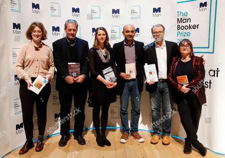 From left, Author Fiona Mozley with her book 'Elmet', Author Paul Auster with his book '4321', Author Emily Fridlund with her book 'History of Wolves', Author Mohsin Hamid with his book 'Exit West', Author George Saunders with his book 'Lincoln in the Bardo' and Author Ali Smith with her book 'Autumn' during a photocall with all six shortlisted authors of the 2017 Man Booker Prize for Fiction, in London, . The winner of the award will be announced Tuesday at a ceremony in London