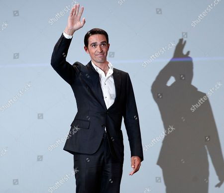 Spain's Alberto Contador, waves as he arrives for the presentation of the 2018 Tour de France cycling race, in Paris, . The 105th edition of the race starts on July 7 2018 to end on the Champs-Elysees avenue on July 29