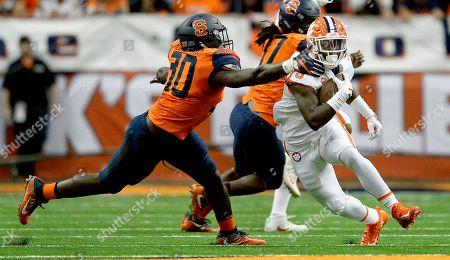 Stock Image of Clemson running back Travis Etienne (9) is grabbed by Syracuse linebacker Parris Bennett (30) during the first half of an NCAA college football game, in Syracuse, N.Y. Syracuse upset Clemson 27-24