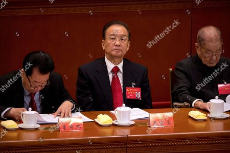 """Former Chinese Premier Wen Jiabao, center, listens to a speech by Chinese President Xi Jinping during the opening session of China's 19th Party Congress at the Great Hall of the People in Beijing, . Xi on Wednesday urged a reinvigorated Communist Party to take on a more forceful role in society and economic development to better address """"grim"""" challenges facing the country as he opened a twice-a-decade national congress"""