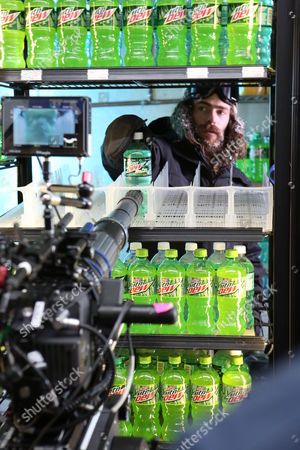 """IMAGE DISTRIBUTED FOR MOUNTAIN DEW - Professional snowboarder Danny Davis stocks a convenience store cooler with bottles of Mtn Dew Baja Blast while filming the Mtn Dew Baja Blast """"Baja Breakout"""" video, on Thurs., in Los Angeles. Davis appears in the short film, debuting today, Tues., May 6, along with racing champion Dale Earnhardt Jr. and professional skateboarder Paul """"P-Rod"""" Rodriguez. Mountain Dew recently announced that, for the first time, Mtn Dew Baja Blast - which was introduced 10 years ago as a """"Taco Bell Original"""" - will also be available for a limited time in bottles and cans. The tropical lim flavored beverage started hitting shelves on Mon., May 5, 2014"""