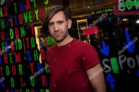 Stock Image of Stuart Semple poses in front of his artwork upon arrival at the Artist in Residence Party in London