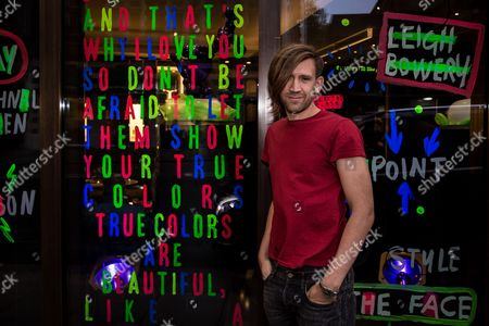 Stock Picture of Stuart Semple poses in front of his artwork upon arrival at the Artist in Residence Party in London