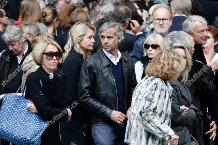 French actor Paul Belmondo, center right, and his wife Luana, center left, arrive to the funeral ceremony for French actor Jean Rochefort at the Saint Thomas d'Aquin church in Paris, . French actor Jean Rochefort, who starred in more than 100 movies over a half-century and was much loved by the French public, has died. He was 87