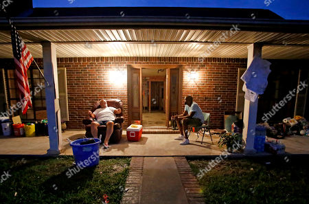"""Cliff Johnson, Gene Jones. Cliff Johnson, left, talks with neighbor Gene Jones outside Johnson's damaged home in a neighborhood that was flooded by Hurricane Harvey in Beaumont, Texas, . Jones, a truck driver who didn't vote, asked Johnson, a Trump supporter, if he thought climate change had intensified the storm. """"I don't think so, no,"""" Johnson replied. """"You don't? You don't think about the chemical plants and the hot, hot weather? You don't think that has anything to do with it?"""" They lost their homes to the flood, and they sat on the porch grappling with the reason why"""