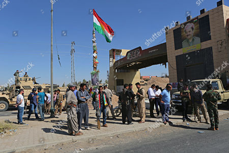 Stock Image of A picture of Massoud Barzani, the President of Iraq's autonomous Kurdish region, and a Kurdish flag are displayed as Kurdish security forces stand guard in Alton Kupri, on the outskirts of Irbil, Iraq, . Kurdish media said Thursday that Iraqi Kurdish officials have postponed elections for parliament and president of the autonomous region originally slated for November 1, in the wake of the withdrawal of Kurdish forces from disputed regions across northern and eastern Iraq