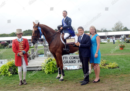 Juan-Carlos Capelli and Jennifer Judkins, of Longines, present Kent Farrington, of Wellington, FL, with a Longines timepiece after winning the $250,000 Grand Prix at the Hampton Classic, in Bridgehampton, NY. Longines is the official watch and timekeeper of the 38th annual Hampton Classic Horse Show