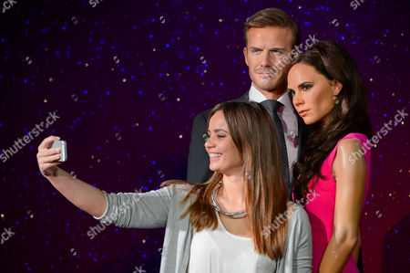 Visitor Stephanie Francis poses for a photo with the wax figures of British personalities, David Beckham and Victoria Beckham by Caryn Bloom, left, and Rebecca Holmes, right, at Madame Tussauds, London