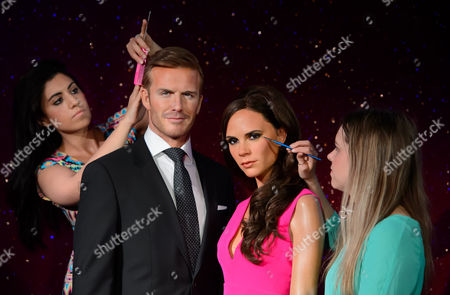 Final adjustments are made to the wax figures of British personalities, David Beckham and Victoria Beckham by Caryn Bloom, left, and Rebecca Holmes, right, at Madame Tussauds, London
