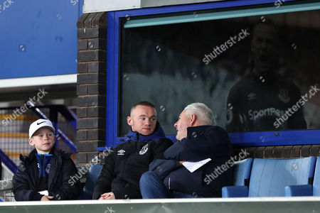 Wayne Rooney sits in a corporate box with his son Kai Rooney and his agent Paul Stretford during the match