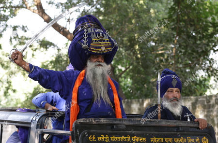 Baba Major Singh, a Sikh man who belongs to the armed Sikh order Nihang, wearing a huge turban brandishes his sword during the Mohalla religious procession on 'Fateh Divas' or 'Victory Day' in Amritsar, India, 20 October 2017. The procession is carried out a day after the Diwali festival to mark the Bandi Chorh Diwas, the day when Guru Hargobind, the sixth Guru or the Master of the Sikhs, reached Amritsar after his release from Gwalior fort, along with 52 other kings with him during the reign of Mughal emperor Jahangir. Each year members of various major Nihang groups display their martial arts and horse riding skills during the Mohalla procession.