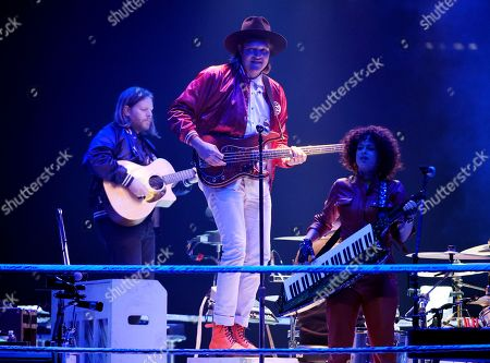 Tim Kingsbury, Win Butler, Regine Chassagne. Left to right, Tim Kingsbury, Win Butler and Regine Chassagne of Arcade Fire perform during the band's concert at The Forum, in Inglewood, Calif
