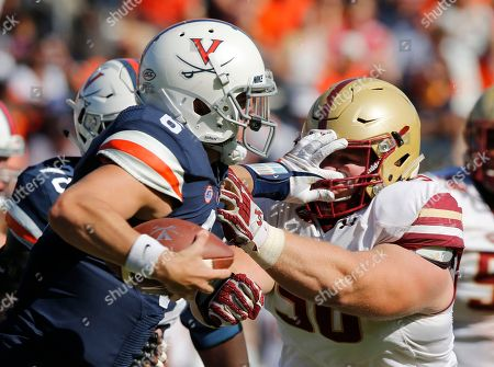Stock Picture of Kurt Benkert, Ray Smith. Virginia quarterback Kurt Benkert (6) stiff arms Boston College defensive tackle Ray Smith (96) during the second half of an NCAA college football game in Charlottesville, Va