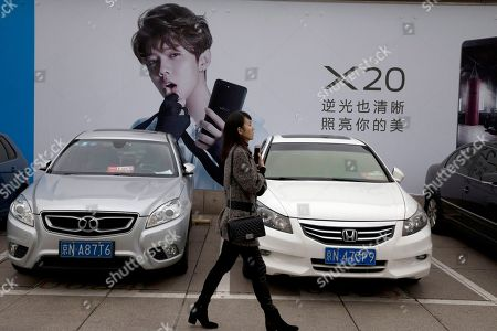 A woman walks past an advertisement featuring teen idol Lu Han, also known as China's Justin Bieber in Beijing, China. China works to stifle celebrities as it seeks to dictate the values the nation's youth should embrace. It's part of the most ambitious effort in years to shape the country's booming entertainment industry. Instead of selfish, rich stars, the state is promoting performers who are all about patriotism, purity and other values that support the party's legitimacy, whether in movies about revolutionary heroes or through rap music